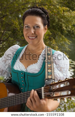 Smiling middle-aged woman in Bavarian Dirndl and braided her hair stands on the lake and playing guitar / Bavarian woman in dirndl smiling while playing guitar at the lake