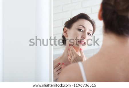 Smiling middle aged woman satisfied with her nature beauty. Cosmetic facial care concept #1196936515