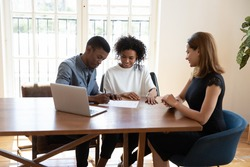 Smiling millennial african american family couple signing contract agreement with female real estate agent at office meeting, discussing deal terms of conditions, purchasing renting leasing apartment.