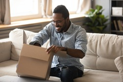 Smiling millennial african american man customer opening cardboard box sit on sofa at home, happy ethnic male consumer unpack parcel receive retail purchase fast postal shipping delivery concept