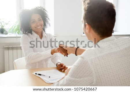 Smiling millennial african woman handshaking partner at office meeting, happy black female manager and satisfied male client or colleague shaking hands making deal or thanking for help in teamwork