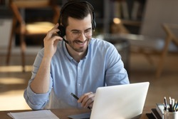 Smiling millennial Caucasian man in headset look at laptop screen work online from home office. Happy young man in headphones watch webinar take course or training on web. Distant education concept.