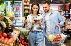 Smiling Millennial Couple Shopping Groceries In The Hypermarket, Two Happy Consumers Buying Food Walking With Cart In Wholesale Shop, Choosing Eco Vegetables And Fruits, Checking Label And Expiry Date