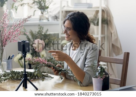 Smiling millennial female florist record video broadcast or course on smartphone compose arrange floral decorations. Happy woman designer shoot vlog on cellphone of flower bouquet composition making.