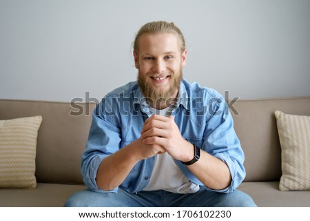 Smiling millennial hipster guy blogger looking at camera video calling, recording vlog. Happy young man distance chatting at home office, streaming sitting on sofa. Headshot portrait. Webcam view