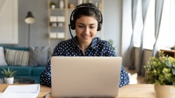 Smiling millennial Indian girl in wireless headset sit at desk in living room study online on laptop, happy young ethnic female in headphones watch webinar or course on Internet on computer