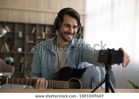 Smiling millennial male artist blogger playing on guitar shooting music video or tutorial on modern smartphone at home studio. Happy young man singer use music instrument, compose song on cellphone.