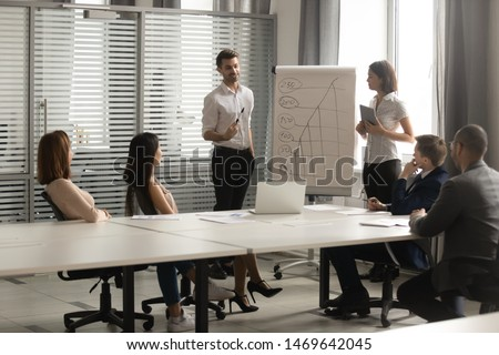 Smiling millennial male presenter stand talking making presentation on flip chart at office briefing, young man coach speak explaining teaching diverse employees drawing on whiteboard at meeting