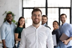 Smiling millennial student looking at camera posing for portrait in front of diverse young people group getting education at international university, happy ambitious intern receiving job at company