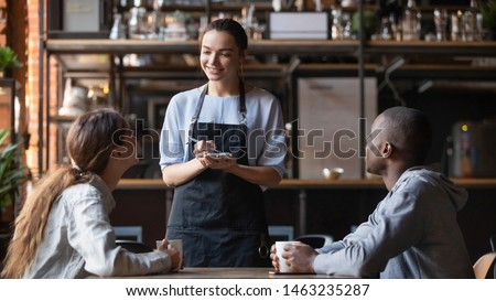 Smiling millennial waitress with notebook taking order from young multiracial client couple, diverse friends relax hang out in cafe or restaurant speak with staff enjoying good service and atmosphere
