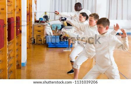 Smiling mixed age group of athletes at fencing workout, training attack movements on mannequins