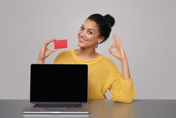 Smiling mixed race african american - caucasian woman showing blank black laptop computer screen and blank credit card, sitting at table and showing OK sign, over gray background