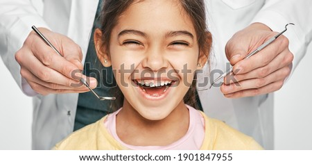Smiling mixed race girl in a dental clinic for children. Child with a toothy smile during inspection of oral cavity by a dentist. Close-up Foto stock ©