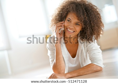 Smiling mixed-race girl laying on floor at home and talking on phone