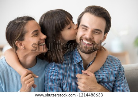 Smiling mixed race mother beautiful daughter and caucasian father sitting on couch at home. Adorable preschool child embrace parents kissing on cheek daddy. Head shot happy multi-ethnic family concept