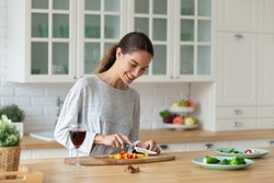 Smiling mixed race woman using knife, cutting fresh vegetables on wooden board in modern kitchen. Happy young girl preparing food alone for romantic dinner night or party with friends at home.