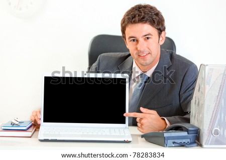 Smiling  modern businessman sitting at office desk and pointing finger on laptop with blank screen