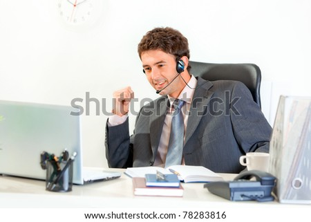 Smiling modern businessman with  headset sitting at office desk and looking  on laptop