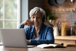 Smiling modern mature 60s Caucasian woman in earphones look at laptop screen watch webinar online at home. Happy senior grey-haired female have fun study on internet. Elderly technology concept.