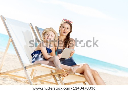 smiling modern mother and child in swimwear on the seashore using tablet PC while sitting on beach chairs Foto stock ©