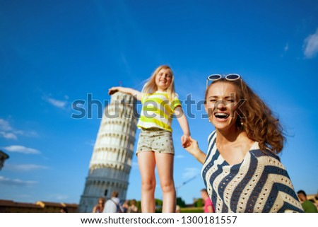 smiling modern mother and daughter posing for tourist picture against leaning tower in Pisa, Italy. taking silly photographs is a must here. having micro holidays. can't avoid crowds here. blue sky