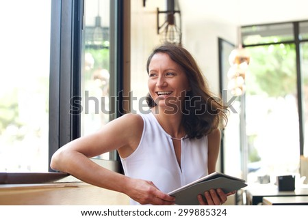 Smiling modern older woman sitting at cafe with tablet