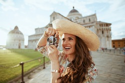 smiling modern woman in floral dress with retro camera and hat in piazza dei miracoli in Pisa, Italy.