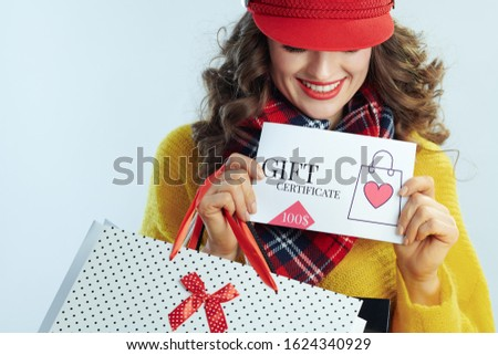 smiling modern woman with long brunette hair in sweater, scarf and red hat with shopping bags showing gift certificate isolated on winter light blue background.