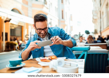 Photo of Smiling modern young man taking picture of his meal