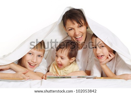 smiling mom with her children are lie on the floor
