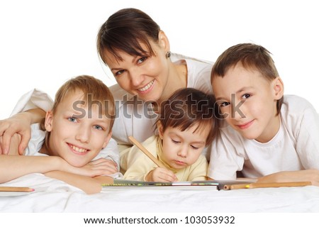 smiling mom with her young children are lie on the floor