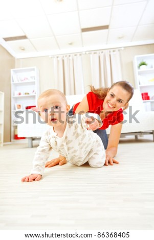 Smiling mommy playing with creeping on floor baby