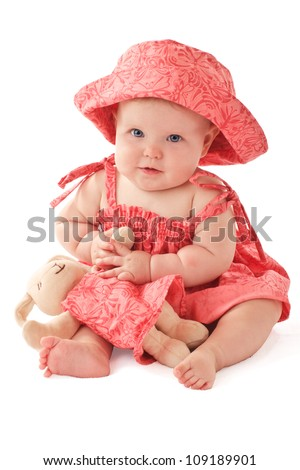 Smiling 6 month old baby girl sits holding a stuffed toy bunny rabbit. Baby's strawberry pink floral hat and sun dress match the toy. Vertical, copy space, isolated on white.
