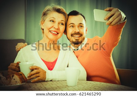 Smiling mother and adult son photographing together at home