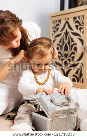 Smiling mother and baby daughter playing with jewelry
