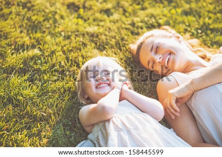 Smiling mother and baby laying on meadow