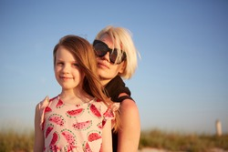 Smiling mother and beautiful daughter having fun on the beach. Portrait of happy woman giving a piggyback ride to cute little girl with copy space. Portrait of kid embracing her mom during summer.