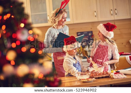 smiling mother and children baking cookies at home on Xmas eve