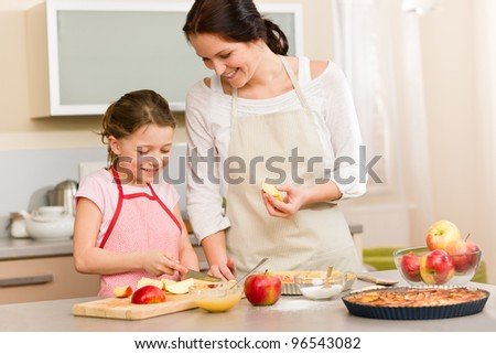 Smiling mother and daughter cutting apples for baking a pie