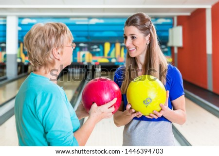Smiling mother and daughter holding bowling ball enjoying indoor game