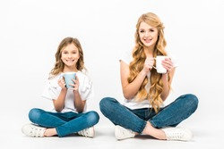 smiling mother and daughter holding coffee cups while sitting on floor with crossed legs and looking at camera on white background