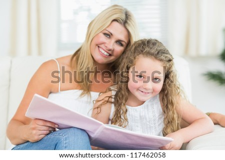 Smiling mother and daughter sitting on the sofa with a book