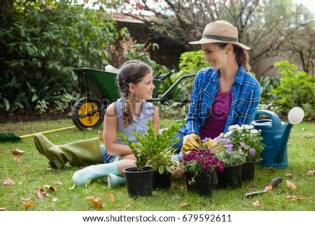 Smiling mother and daughter sitting with various flowering potted plants on field in backyard