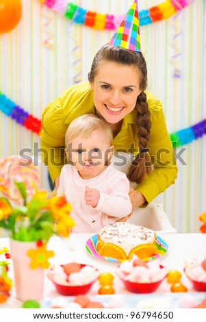 Smiling mother and eat smeared baby on birthday celebration party