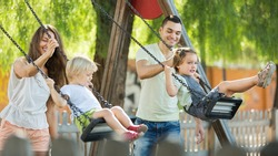 Smiling  mother and father swinging children at park. Focus on woman