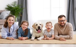 Smiling mother and father with little kids and adorable purebred Labrador retriever dog lying on floor and looking at camera while spending time together at home