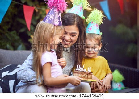 Smiling mother and her boy and girl child's celebrate children birthday party and blowing candle c ストックフォト ©