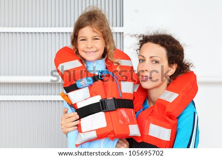 Smiling mother and her daughter wearing in orange life jacket  look at camera at deck of ship