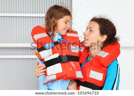 Smiling mother and her daughter wearing in orange life jacket  look at other at deck of ship