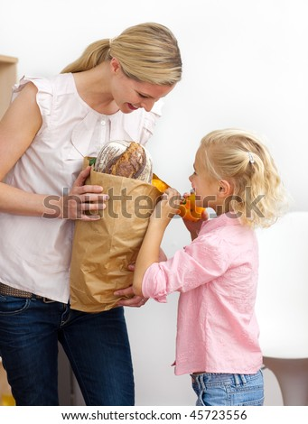 Smiling mother and her Little girl unpacking grocery bag in the kitchen